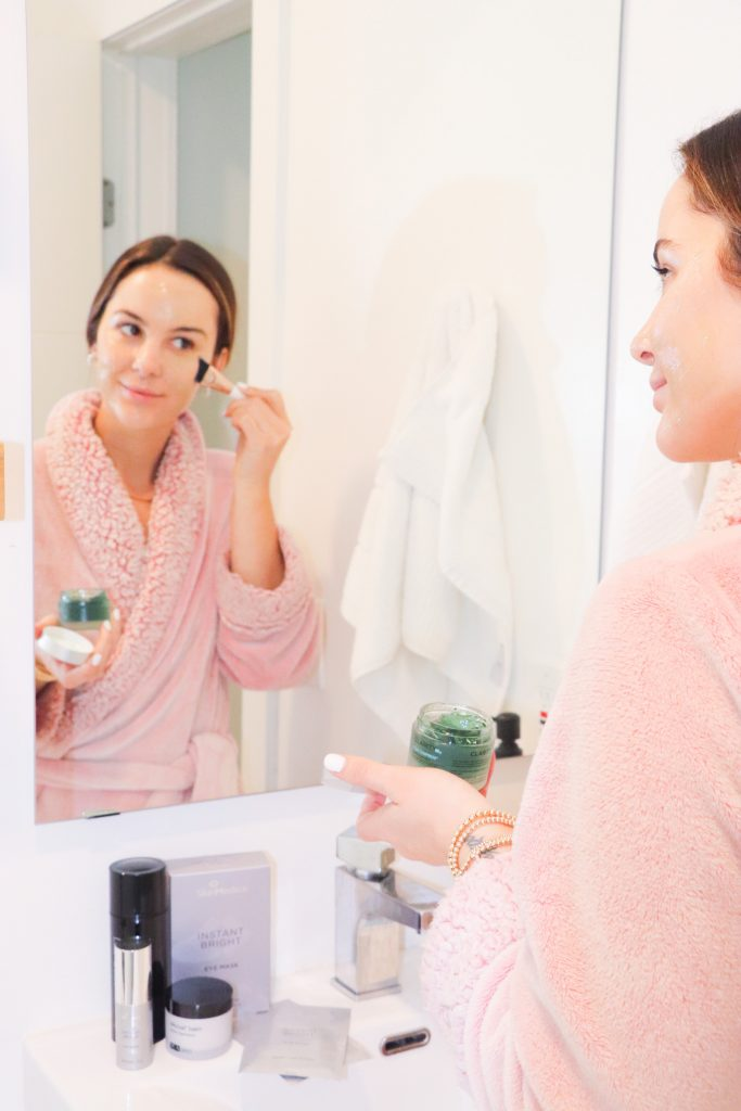 woman applying face mask and doing selfcare for Valentine's Day