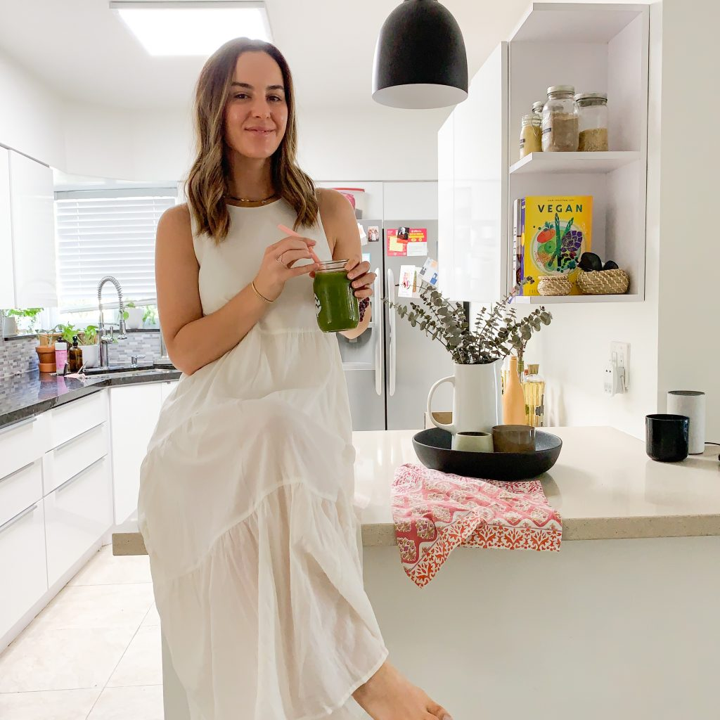 woman sitting on kitchen island and drinking juice with Oral Collagen
