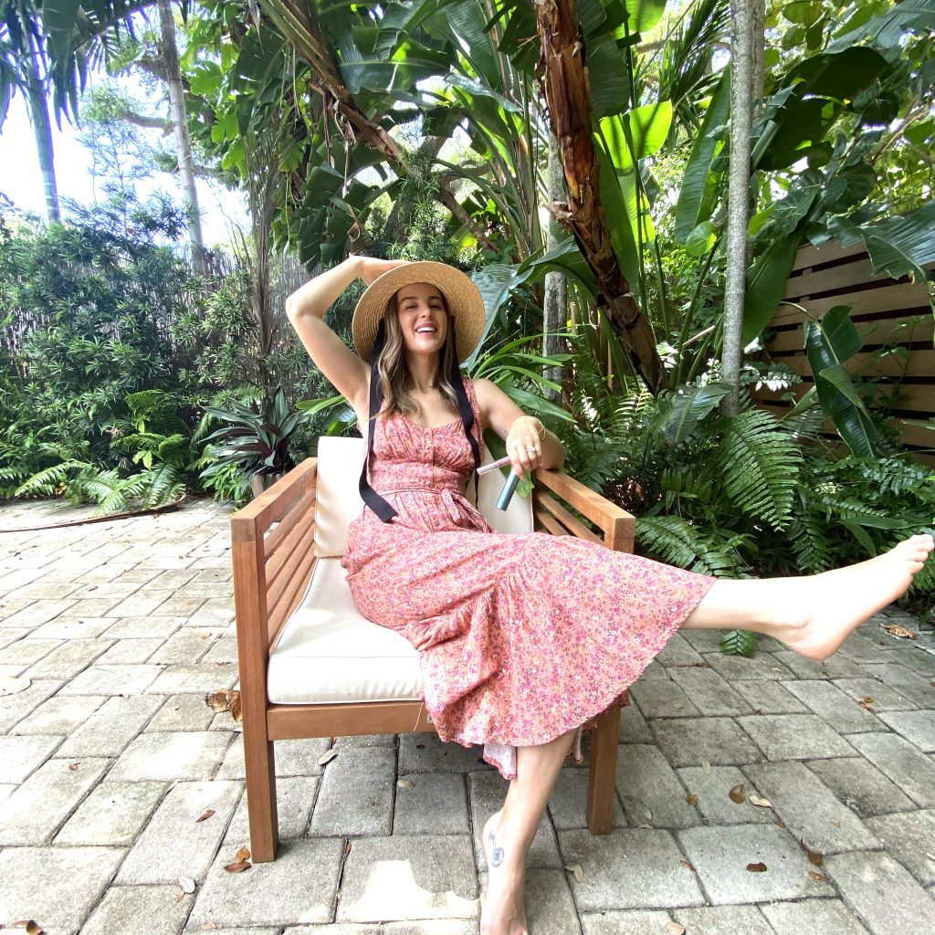 woman wearing a floral dress is sitting in the backyard holding products to avoid Sun Sins